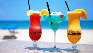 An array of red, blue, and orange cocktails oceanside