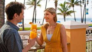 A happy couple enjoying two orange cocktails